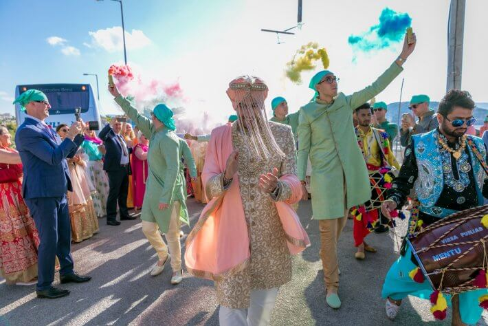 Sikh groom entering wedding venue with Punjabi dhol and his family