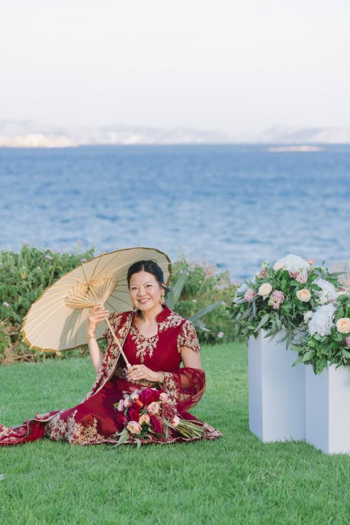 Chinese bride posing with a paper umbrella in Athens Riviera Greece