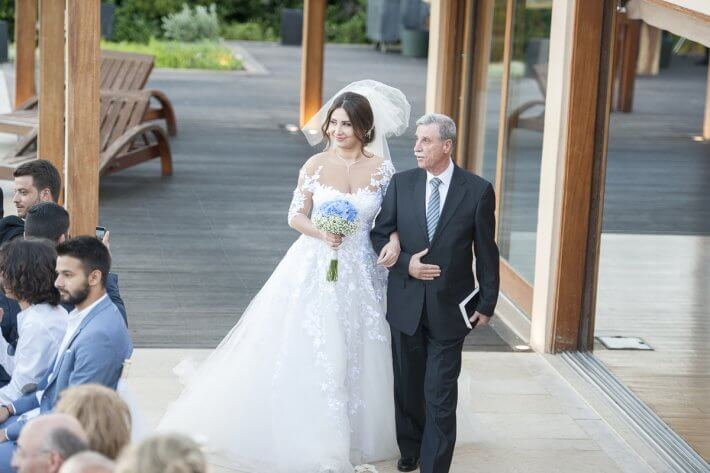 Beautiful bride entering ceremony area with her father in athens riviera wedding venue