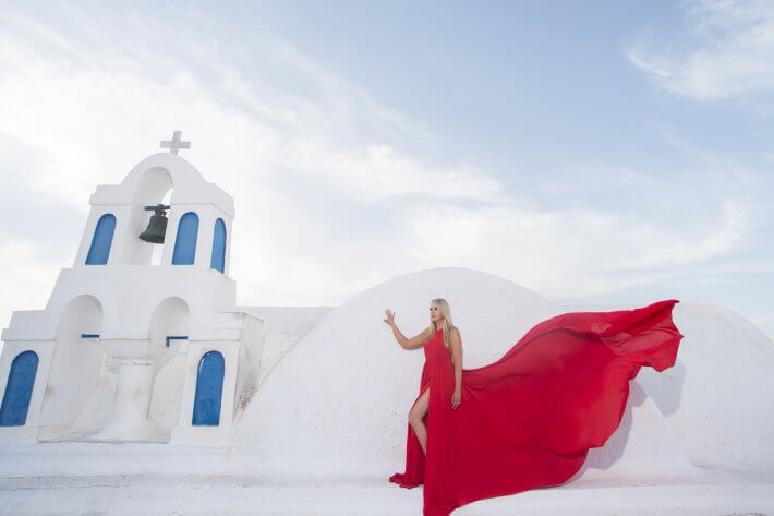 Bride with red dress in front of a chapel Santorini