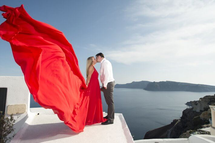 Red dress bride posing in Santorini with her groom
