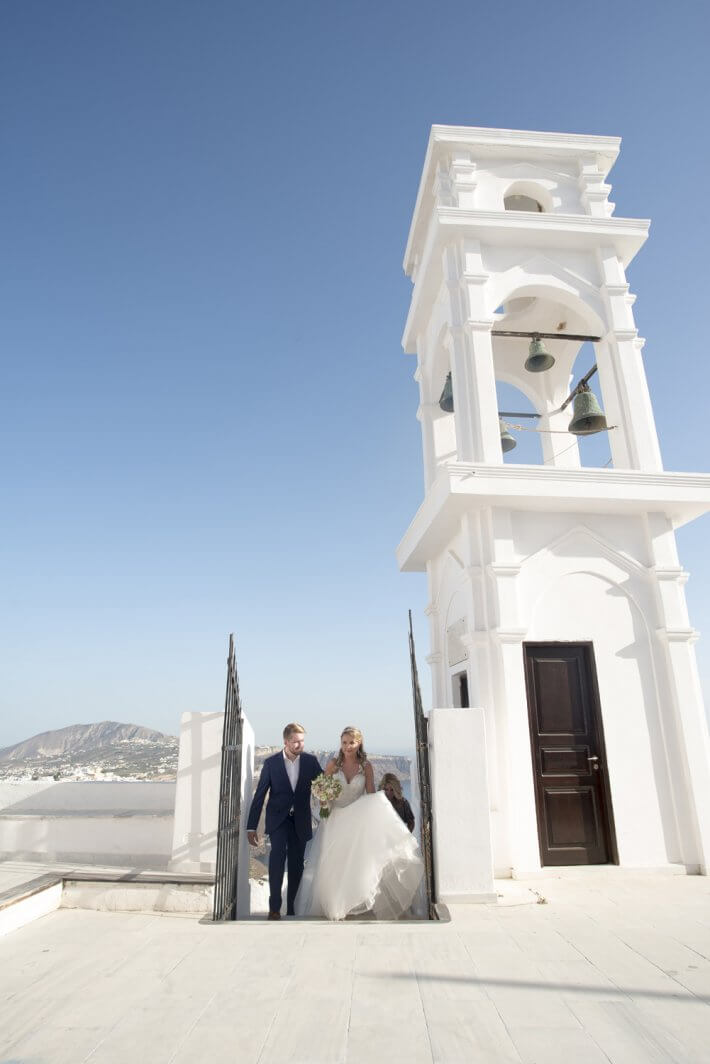 Bride and groom entering Anastasi church for wedding in Santorini