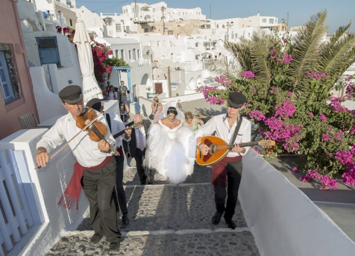 The bride is walking in Santorini Caldera going to the wedding venue